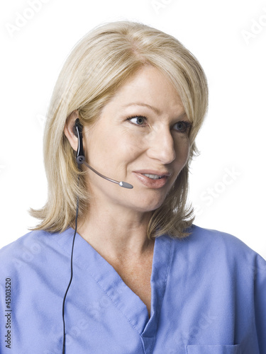 """Female nurse using headset, studio shot"""