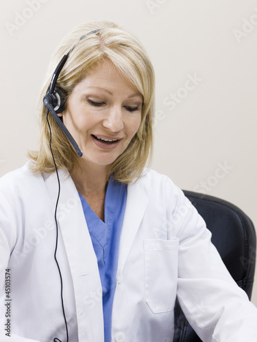 """Mature woman talking on headset, studio shot"""