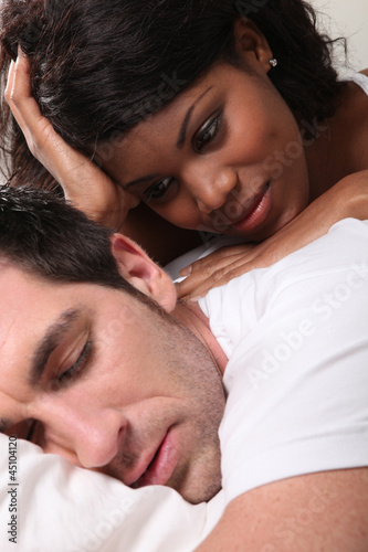 Woman watching man asleep