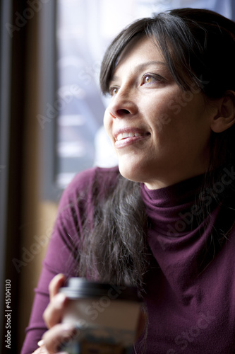 One mid adult woman drinking coffee in cafe