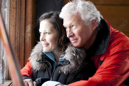 Mature couple looking out of window and embracing