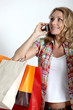 Blond woman holding shopping bags talking on cellphone