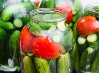 salted cucumber and tomatoes in a jar
