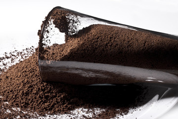 Glass spilling ground coffee