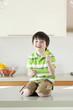 USA, Utah, Portrait of smiling boy (4-5) holding slice of kiwi