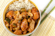 Kung Pao chicken in a bowl with rice and chopsticks