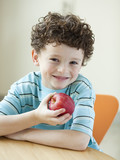 USA, Utah, Portrait of smiling boy (6-7) holding red apple