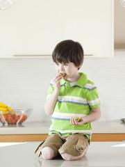 USA, Utah, Boy (4-5) eating kiwi in kitchen
