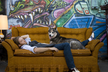USA, Utah, Salt Lake City, Young man sleeping on sofa with dog, graffiti in background
