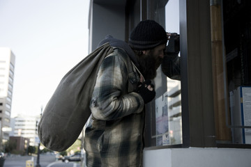 USA, Utah, Salt Lake City, Homeless man looking through window holding sack