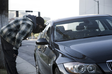 USA, Utah, Salt Lake City, Homeless man peering into car, side view