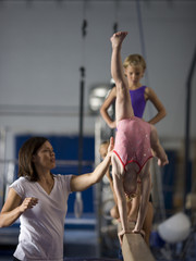 USA, Utah, Orem, Instructor helping gymnasts (6-9) to perform handstand on beam