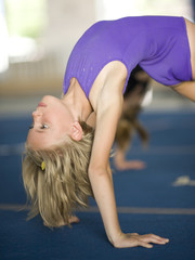 USA, Utah, Orem, Girl (8-9) stretching in gym