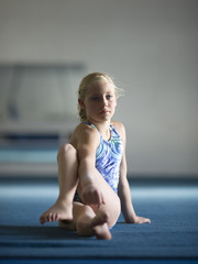 USA, Utah, Orem, Girl (10-11) stretching in gym