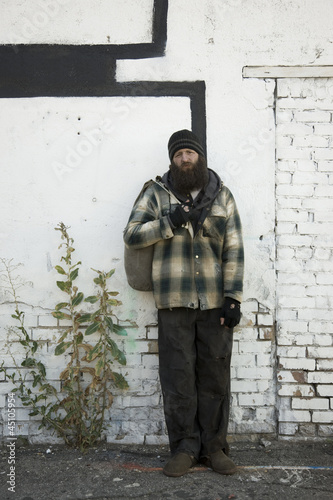 USA, Utah, Salt Lake City, Homeless man standing in front of brick wall