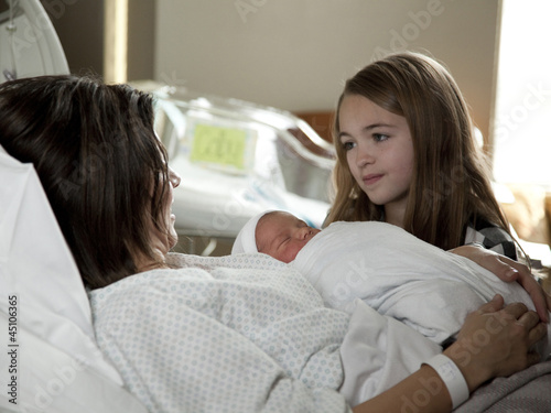 USA, Utah, Payson, Girl (8-9) with mother and baby boy (0-1 months) in bed