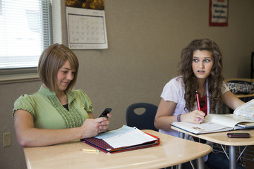 """USA, Utah, Two teenage girls (14-17) working in classroom, one using mobile phone"""