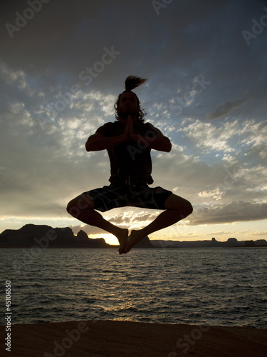 """USA, Utah, Young man jumping by Lake Powell"""