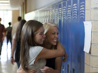 """USA, Utah, Spanish Fork, Two school girls (14-17) embracing in corridor"""