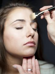 """USA, Utah, Orem, Young woman having make-up applied"""