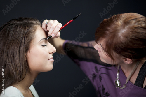 """USA, Utah, Orem, Young woman having make-up applied"""