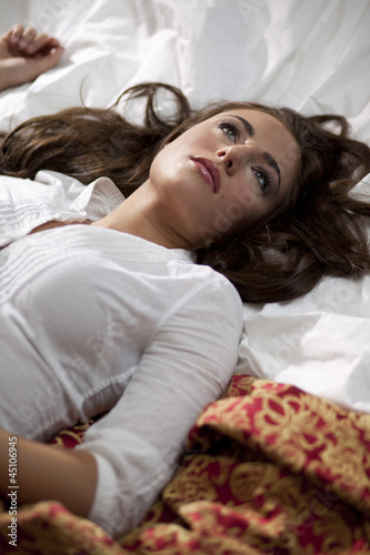 """USA, Utah, Orem, Young woman lying on bed"""