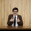 Portrait of businessman giving thumbs up