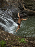 """Costa Rica, Young woman jumping into pool by waterfall"""