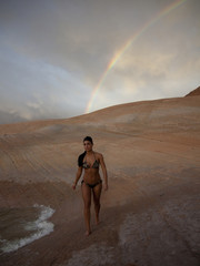 """USA, Utah, Lake Powell, Young woman wearing bikini and walking, rainbow in the background"""