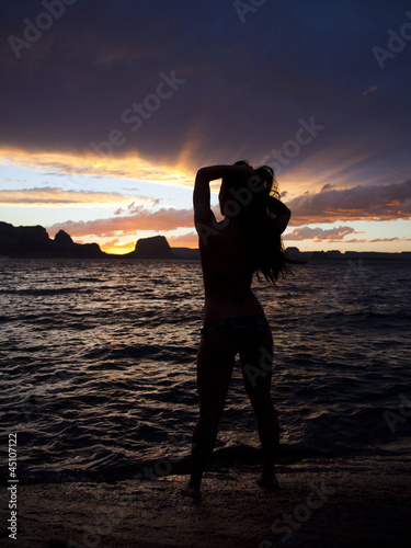 """USA, Utah, Lake Powell, Silhouette of woman standing near lake during sunset"""