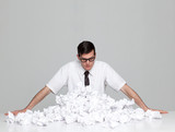 Studio portrait of young man behind stack of paper balls