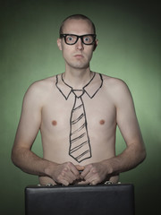 """Portrait of young businessman with tie tattoo, holding briefcase"""