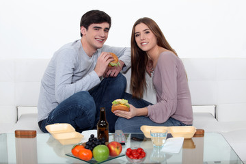 Couple eating fast food in the couch