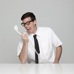 Studio portrait of young man shouting at phone