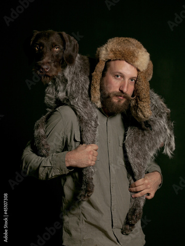 Studio portrait of young man carrying dog over shoulders