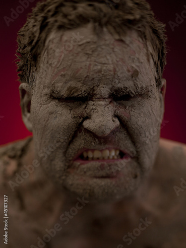 Angry young man covered in mud