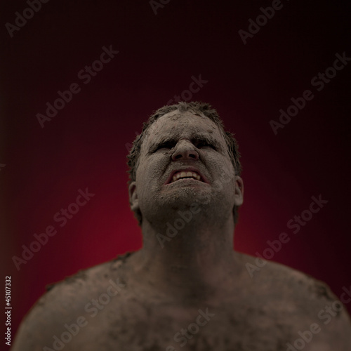 Studio shot of man covered with dirt and mud