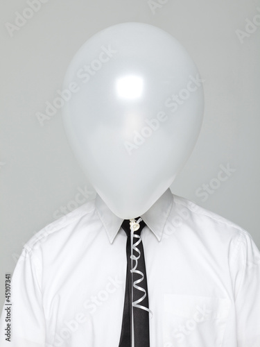 Studio portrait of young man wearing shirt and tie with face covered by white balloon