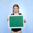 Studio portrait of girl (10-11) holding blank green chalkboard