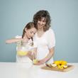 Studio shot of mother assisting daughter (10-11) pouring lemonade
