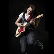 Studio shot of teenage girl (14-15) playing electric guitar and jumping