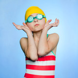 """Studio shot of girl (10-11) wearing swimsuit, swimming cap and swimming goggles"""