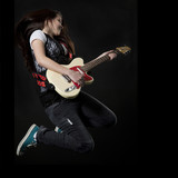 Studio shot of teenage girl (14-15) playing electric guitar and jumping