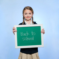 """Studio portrait of girl (10-11) holding green chalkboard with text """"Back to school"""""""