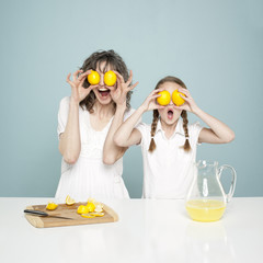 """Studio shot of mother and daughter (10-11) holding lemons, fooling around"""