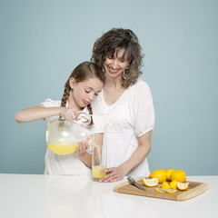 Studio shot of mother assisting daughter (10-11) pouring lemonade