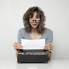Studio shot of surprised woman looking at paper in typewriter