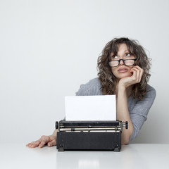 Studio shot of bored woman sitting at table with typewriter