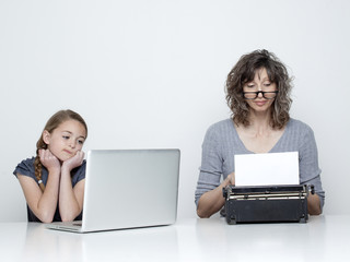 Studio shot of mother using typewriter and daughter (10-11) looking at laptop