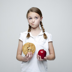 Studio shot of girl (10-11) holding cookie and red apple